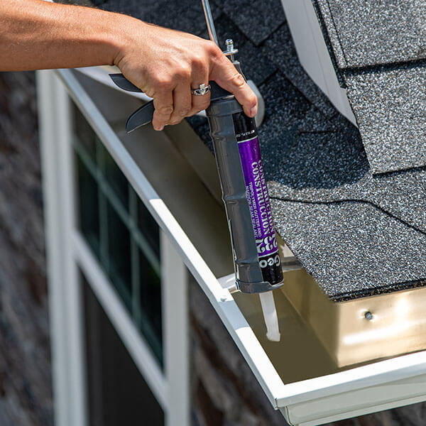 A LeafFilter installers applies caulking to seal clean, white gutters.