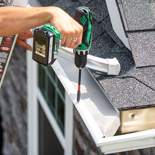 A LeafFilter installer situates gutter protection on clean, white gutters and secures it with a cordless power screwdriver.