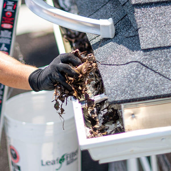 A LeafFilter installer cleans debris from clean, white gutters and places it in a white branded buckets.